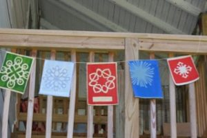 Kirigami Prayer Flags by Elaine Luther as installed on porch.