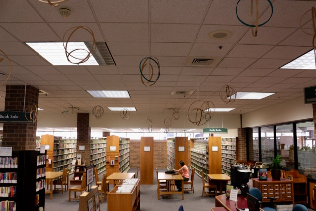 Forest Park Public Library Show of Balance and Tension by Elaine Luther, All artwork is Copyright Elaine Luther 2017. Photo shows a library with bookshelves and tables and an installation of mobiles suspended from the ceiling.