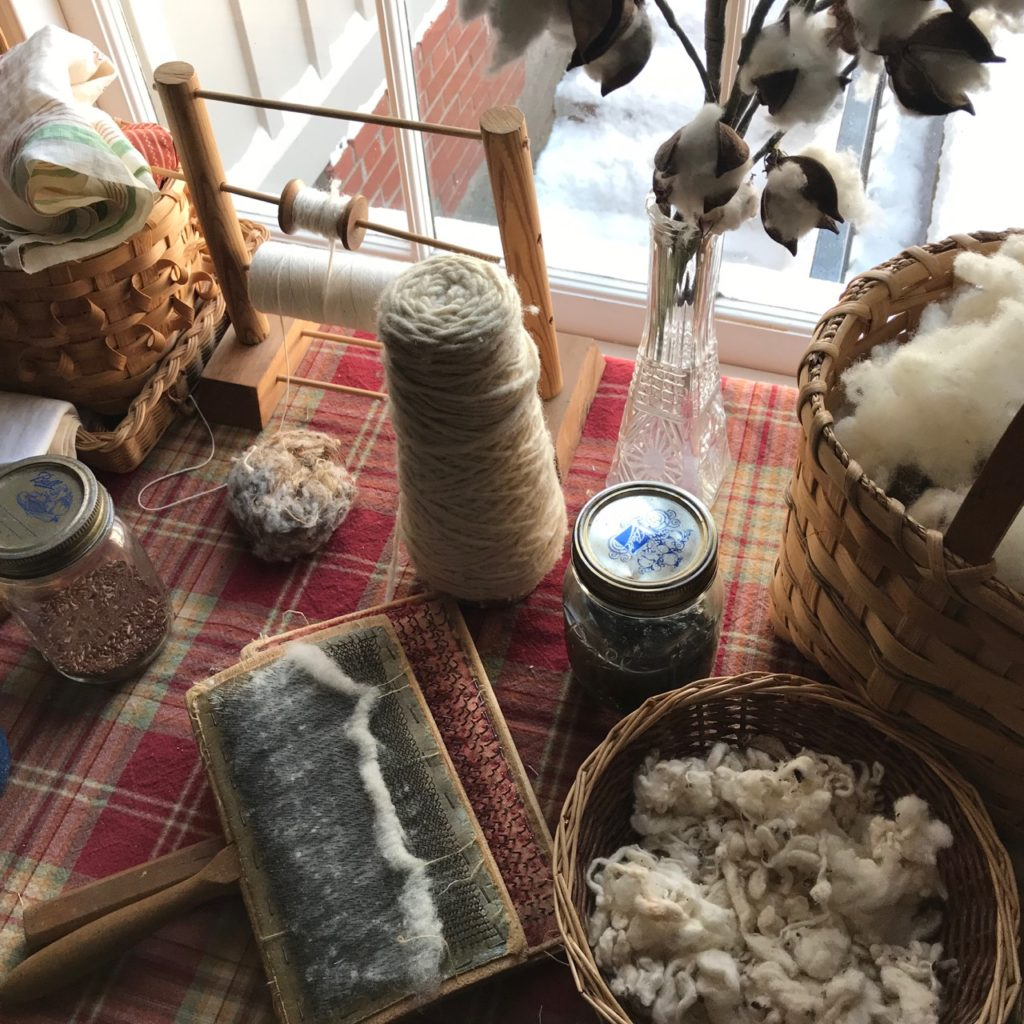 Fiber Production on Farm. A table holds tools for processing wool, such as hand carders, and a bowl of raw wool, a basket of cotton and a branch of a cotton plant in a glass vase.