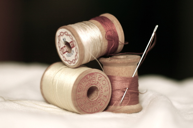 Three wooden spools of thread and a threaded needle.