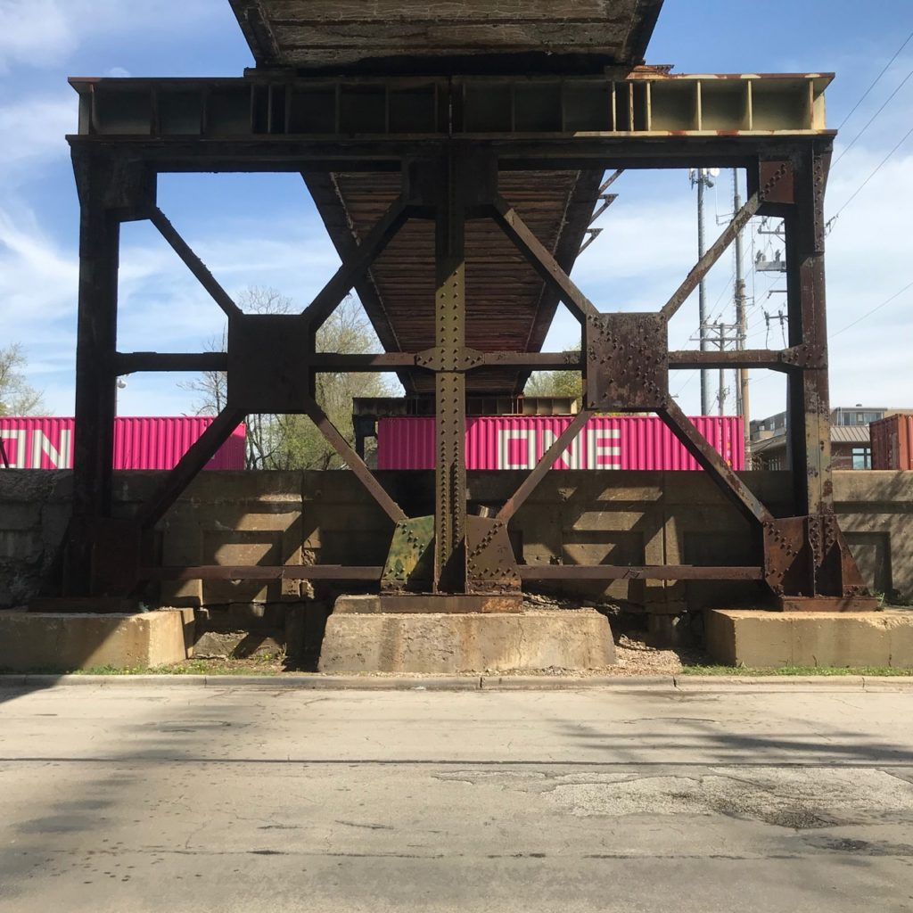 Railroad bridge with pink container cars going by below it. Photo by Elaine Luther, 2020.