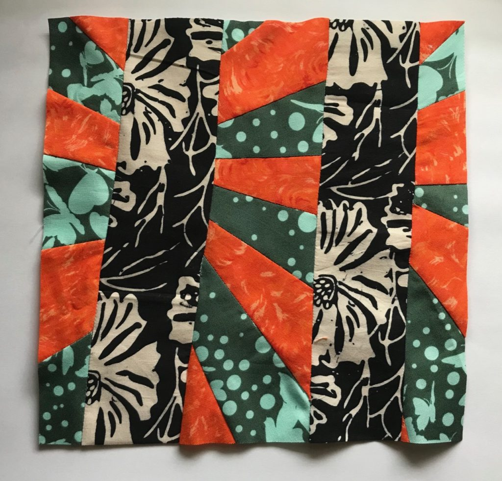 Quilt Block for Pandemic Community Quilt, by Elaine Luther.  The colors of the fabric are orange, black and white and teal.
