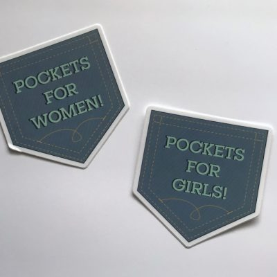 "Pockets for Women! Vinyl Decal Copyright Elaine Luther 2020. Die cut sticker in the shape and color of a jeans pocket says, ""Pockets for Women!"" and another one says, ""Pockets for Girls!"""