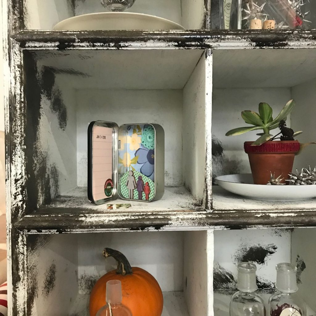 Little art in a tin by Elaine Luther, at The Seed, in the Cabinet of Curiosities. Shelf with multiple small cubbies; cubbies are filled with tiny plants, jars, and a tin with hinged lid, standing upright and open, to show a tiny scene.