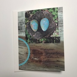 Digital collage card by Elaine Luther has a photo of two egg shapes that are copper with a verdigris patina, resting on a stump. Additional elements include a blue arch, wooden planks and text in French.