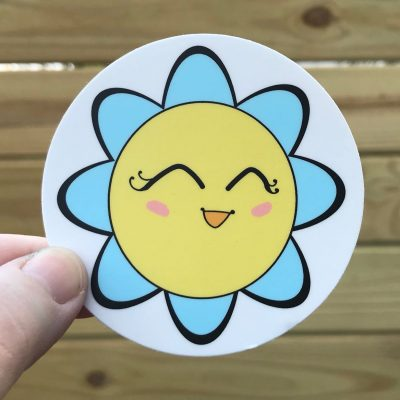 Happy Flower Sticker, Copyright Maria Romero Luther 2018. Sunny yellow flower is smiling with its eyes close, it's petals are light blue.