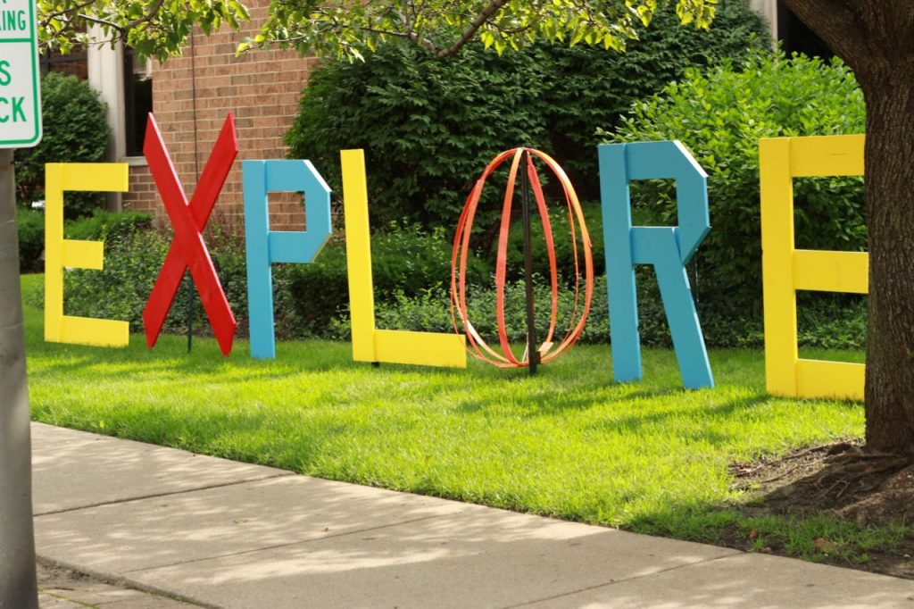EXPLORE installation by Elaine Luther. Brightly painted, the word EXPLORE. The letters are flat and made out of wooden boards, except for the O which is made out of plastic strips forming a globe like shape.