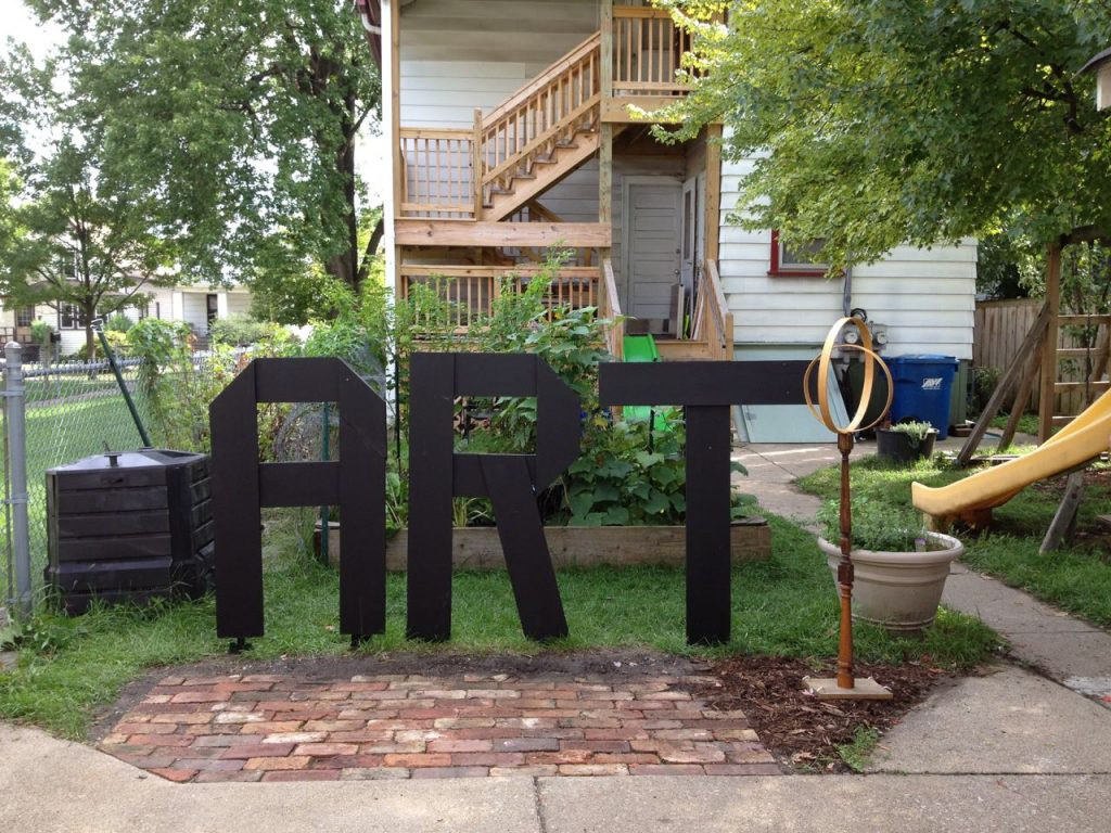 The word ART, built out of wood and painted with black chalkboard paint. By Elaine Luther.