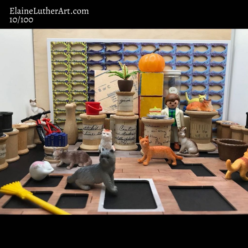 A cluttered miniature space is filled with many tiny plastic cats, a mini bike, a broom, some plants, a basket, a pumpkin, two bowling pins, a plastic bucket, a miniature painting, and more. Along the back wall is a sheet from a game, with punched out fish shapes. Somewhere in the scene is a woman, barely visible. One cat investigates a knocked over bowl of cream.