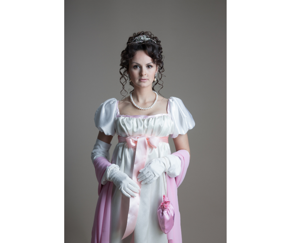 A modern day woman in a white dress with a high waist wears white gloves and carries a pink reticule. The dress has a pink ribbon around the ribcage.