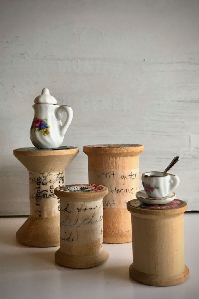 A wooden spools and miniature tea set photo by Elaine Luther, October 2020. A group of 4 wooden spools, most with text wrapped around them. A tall spool has a dollhouse teapot on it and a lower spool has a teacup with spoon and saucer.