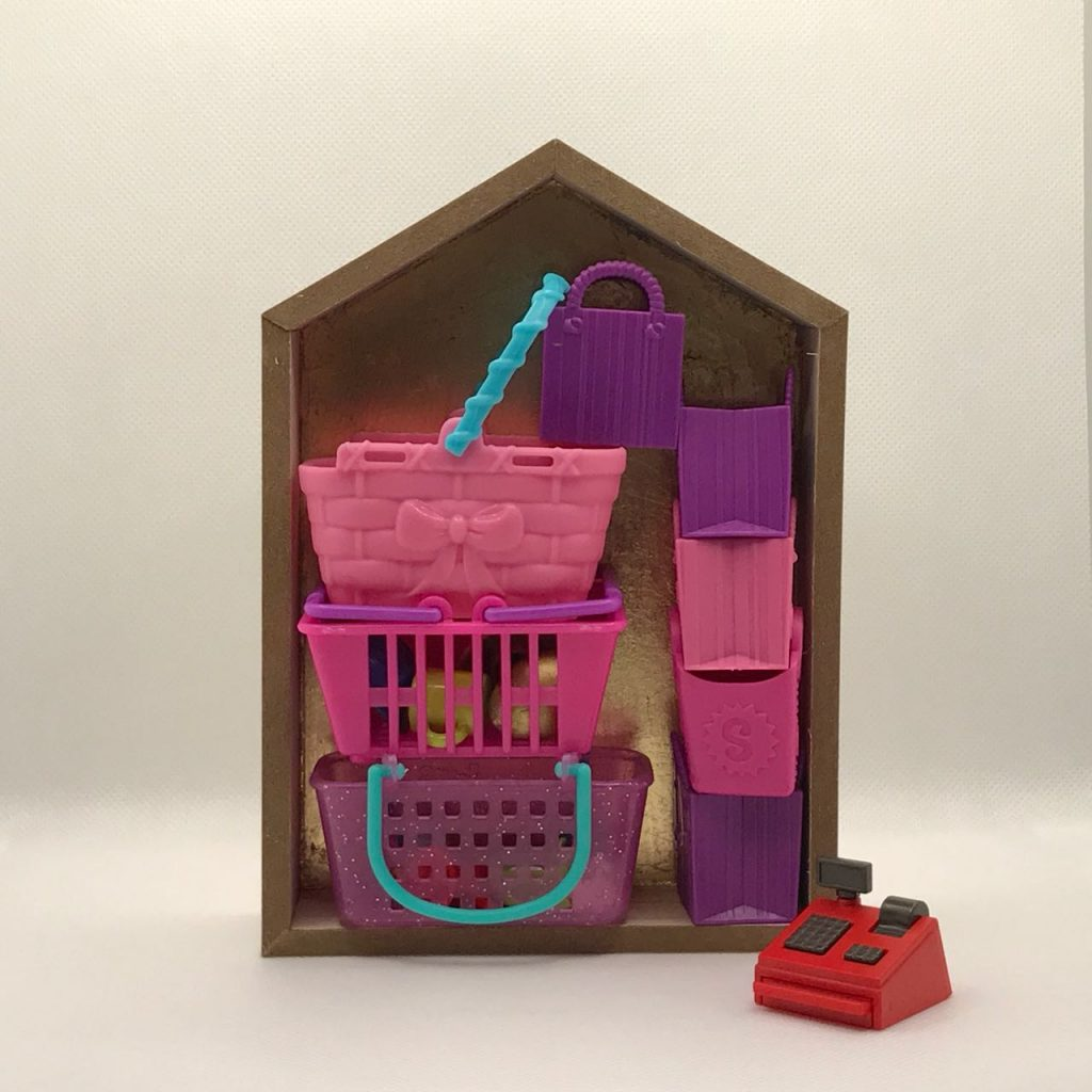 """""""More Work for Mother 4,"""" by Elaine Luther, 2021.  A small house form is filled with plastic shopping baskets, filled with small, random items, and rubber shopping bags.  A tiny cash register sits just outside the house form.  The baskets are all pink or purple.  The cash register is red."""
