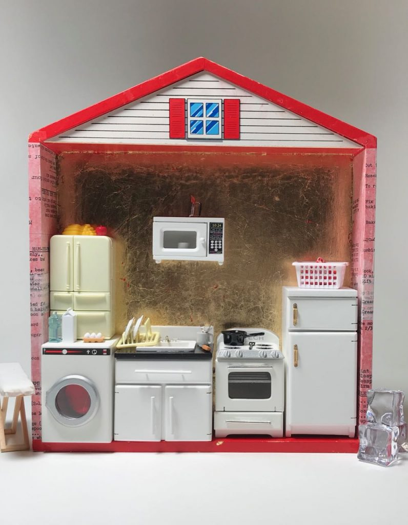 """""""More Work for Mother"""" by Elaine Luther, 2021.  A red box, about 3"""" deep is in the shape of a simple house, with a peaked roof.  The back wall is gold-leafed.  The sides are collaged with bits of text on tracing paper.  The inside is crowded with appliance: a washing machine, kitchen sink and cabinet, two fridges, one microwave and one stove.  An iron sits atop the microwave.  An ironing board is just outside the house on the left.  Cubes of acrylic """"ice"""" are the to right of the house form.  Various foods are scattered about.  A laundry hamper sits atop one fridge.  Dishes are in the sink and in the drain rack."""