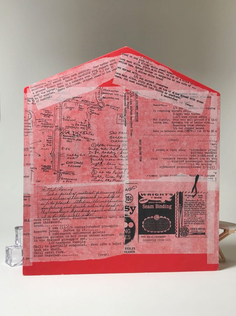 """Side view. """"More Work for Mother"""" by Elaine Luther, 2021. A red box, about 3"""" deep is in the shape of a simple house, with a peaked roof. The back of the house is collaged with black text and a hand drawn map on tissue paper."""