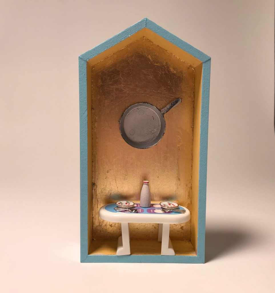 """""""More Work for Mother 5,"""" by Elaine Luther, 2021.  A small house form is painted robin's egg blue and the back inside wall is gold leafed.  A tiny plastic table is set with tiny ceramic dishes with cherries painted on them, a wooden jug of milk and tiny utensils.  A silver painted frying pan is affixed to the back wall, above the table."""