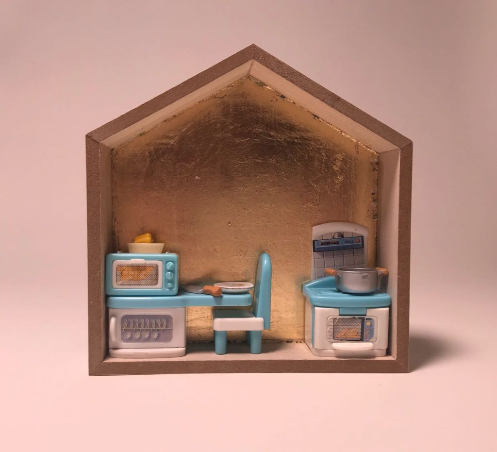 """""""More Work for Mother 2,"""" by Elaine Luther, 2021. A small house form is gold leafed on the back wall and is filled with a tiny scene of plastic dollhouse furniture for a kitchen scene. The stove has a pot on it, there's a knife on the table, a bell pepper sits atop the microwave."""