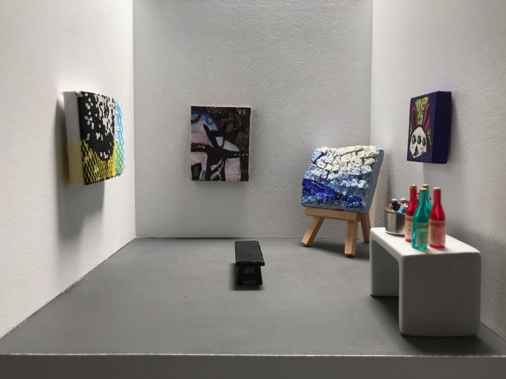 A white box with gray floor has mini art exhibited on the walls and one piece is on an easel. There is also a bench in the center of the gallery and a side table with mini drinks.