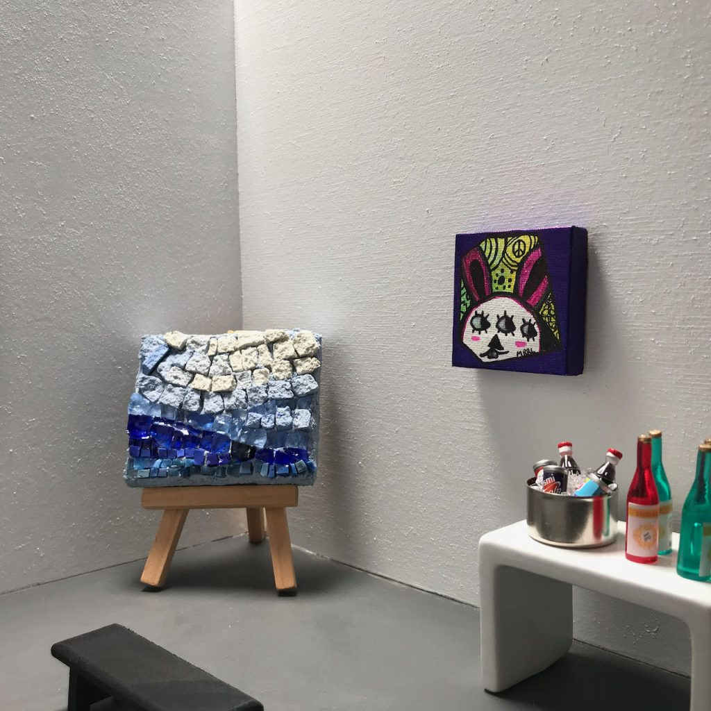 A white box with gray floor has mini art exhibited on the walls and on an easel. There is also a bench in the center of the gallery and against one wall, a table holding drinks.