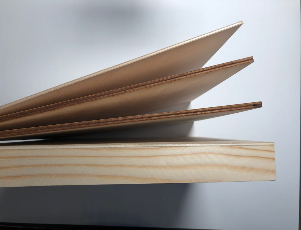 A photo shows four pieces of wood, viewed from the top, or edge, so that you can see the relative thickness of all the parts.