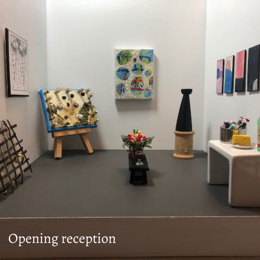 """A view of an art exhibition at the Angelica Kauffman Gallery, a 12"""" x 12"""" x 12"""" gallery. You can see art on the wall, a sculpture in the corner, a woven metal piece leaning against the wall. A table holds wine, cheese and soda. A bench holds flowers and a wine glass."""