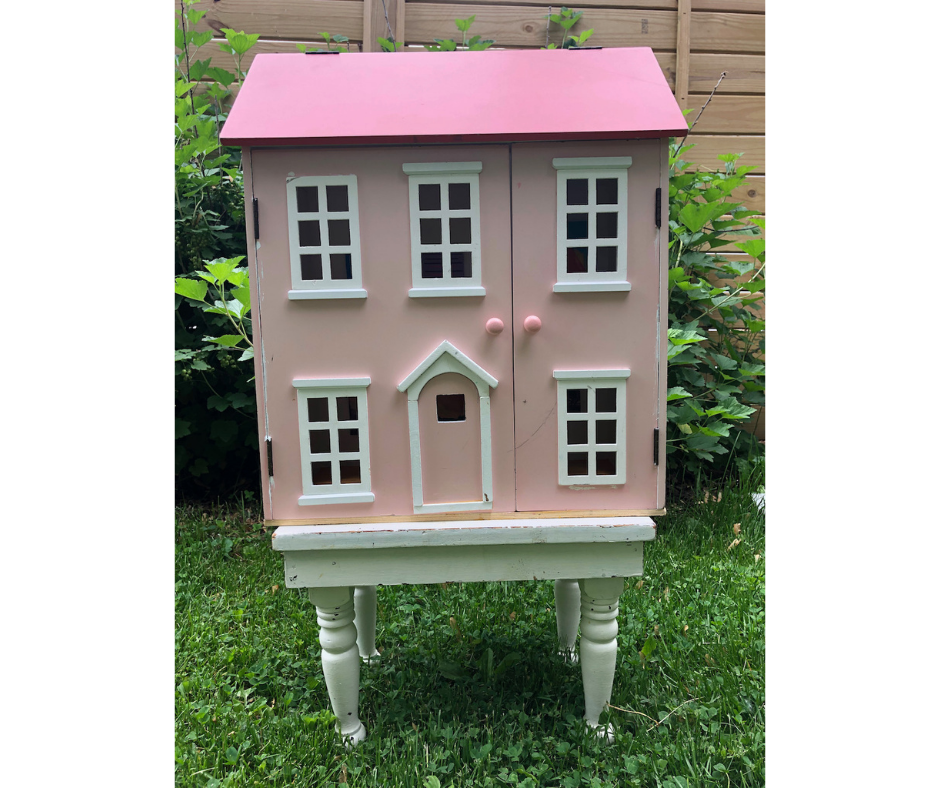 The Angelica Kauffman Dollhouse Art Center by Elaine Luther.  A pink and white dollhouse is on a white footstool in the grass.