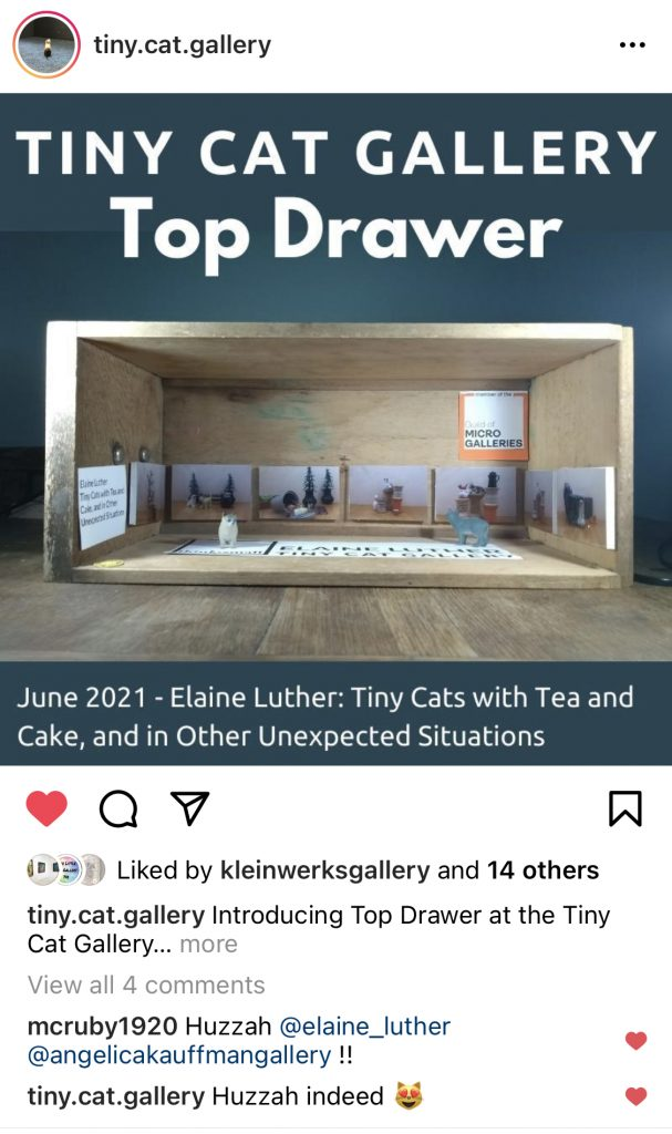 A screenshot from Instagram from the Tiny Cat Gallery, showing an art show of photos by Elaine Luther. In the gallery are two cats.