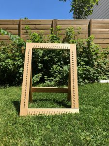 A wood loom that's a rectangle and has screws all around the edges. It has an easel back and was photographed outdoors.