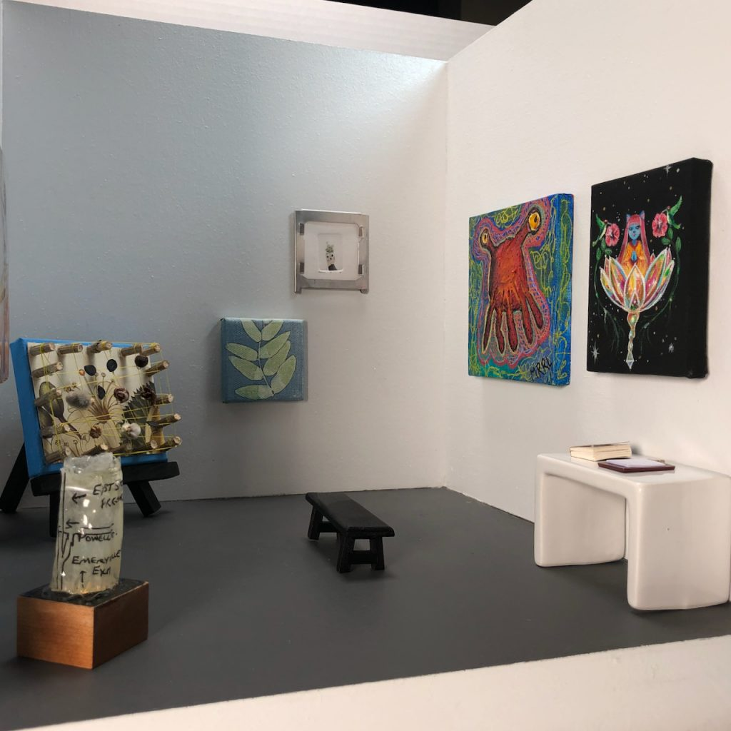 """Art in a 12"""" x 12"""" box gallery, with bench and table."""