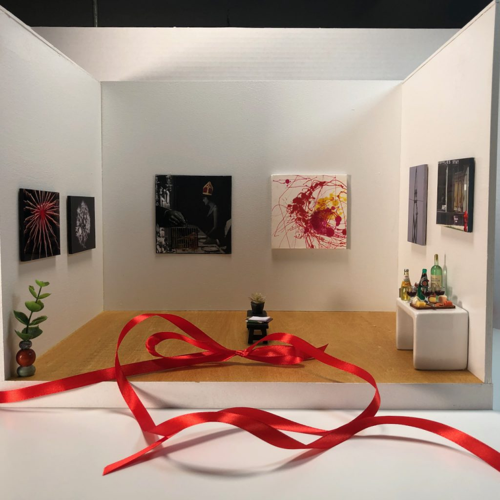 """An image of a 12"""" x 16"""" micro gallery with art installed and drinks for a miniature reception."""