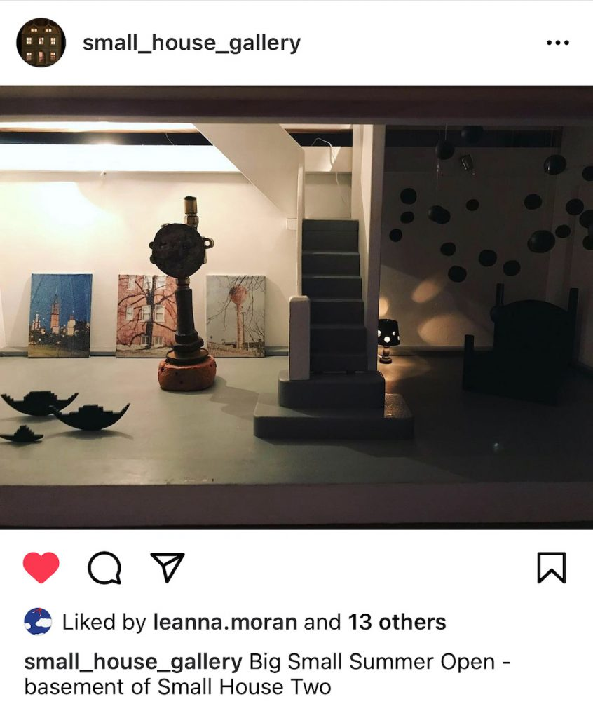 The lower level of a dollhouse art gallery in London. The gallery is called the Small House Gallery. There are several sculptures and three photos, printed on aluminum foil and mounted on wood, are leaning against the back wall. Photos on foil are by Elaine Luther.