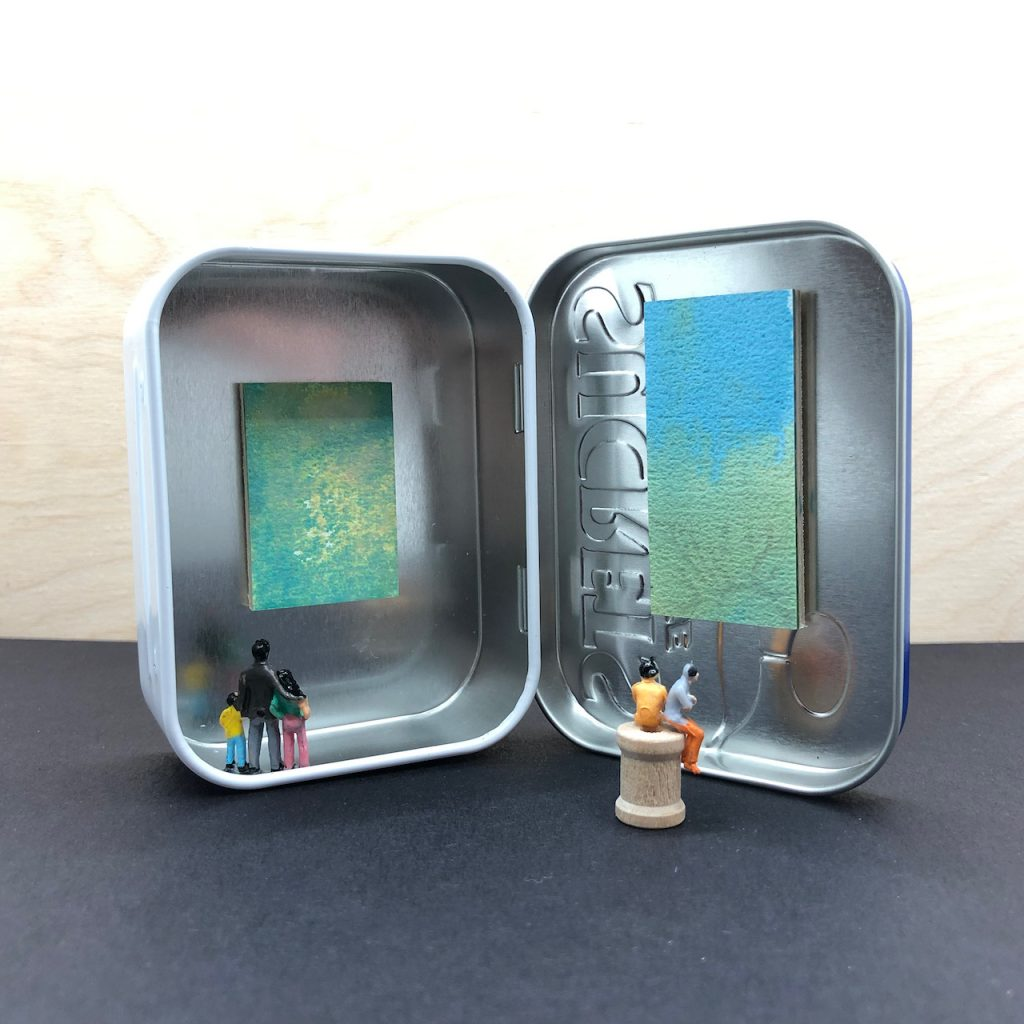 A tin with hinged lid stands on end and open. One work of art on wood panel is on each side of the tin. Tiny model railroad people admire the art.