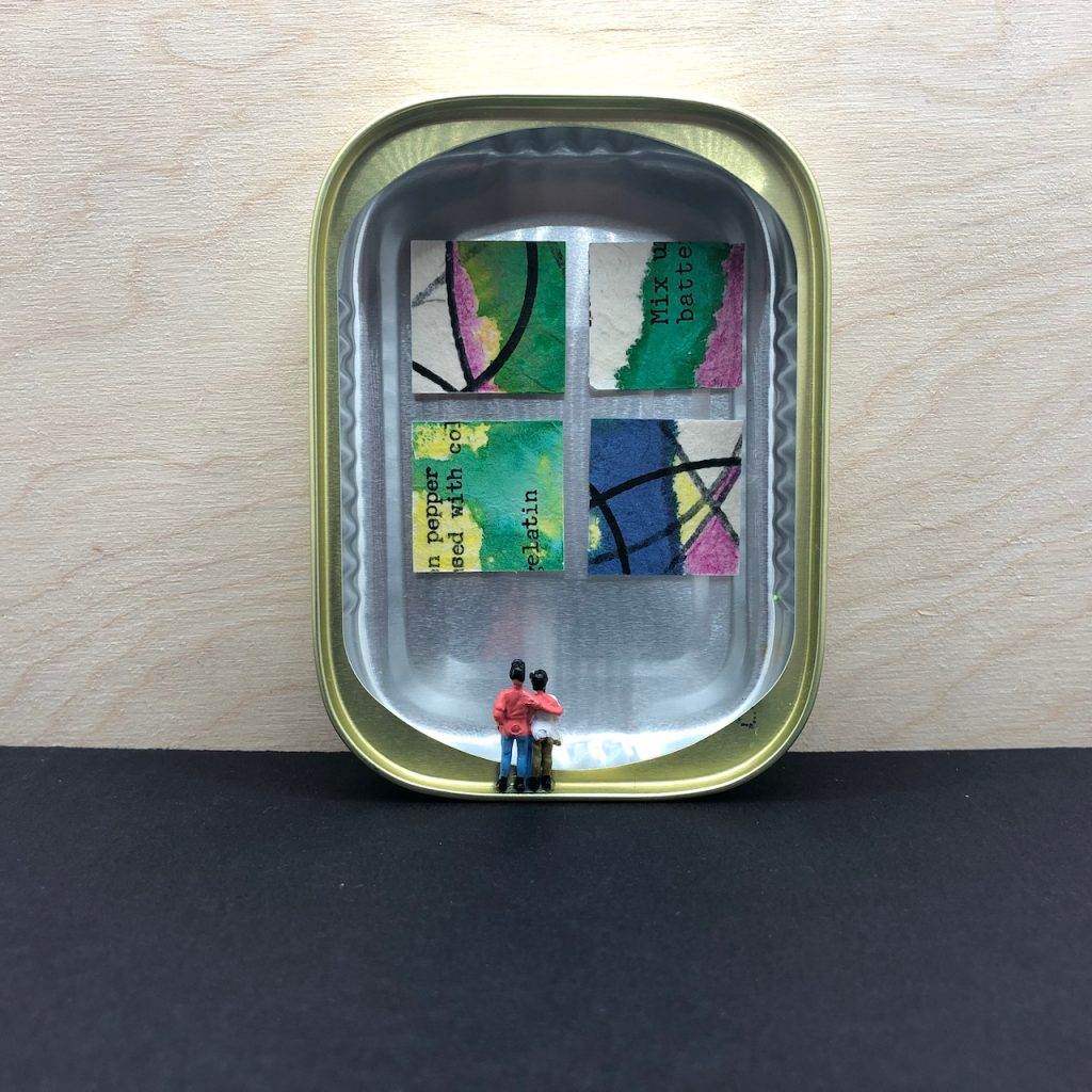 """A tin that originally held sardines stands on end. Four works of art, each one just 1"""" x 1"""", are displayed in the micro-micro gallery. Tiny model railroad people admire the art, one person has their arm over the shoulder of the other."""