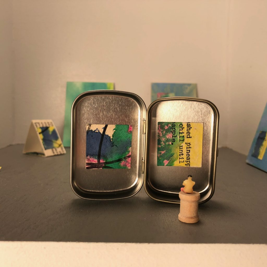 """Micro-micro Gallery in a very small mint tin, with 1"""" square artwork by Elaine Luther."""