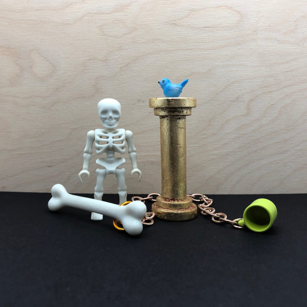 The Award for the Perfect Tweet created by Elaine Luther. This version includes a PlayMobil skeleton in addition to the gold leafed column, blue bird, chain, bone and common cup.